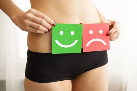 Woman Health Problem. Closeup Of Female With Fit Slim Body In Panties Holding Two Card With Sad Smiley And Happy Face Near Her Stomach. Digestive Disorders, Period Pain, Health Issues Concept Stock Photo