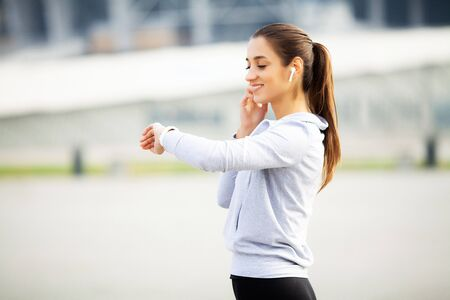 Sports woman doing exercises and listening to music in the urban environment