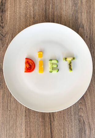 Word DIET made of sliced vegetables in white plate on wood background.