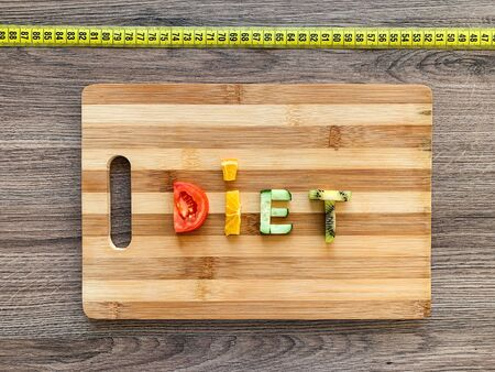 Diet written with vegetables in healthy nutrition concept on wooden board.