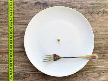 Diet. Suffering from anorexia. Cropped image pea on white plate, with fork and measuring.
