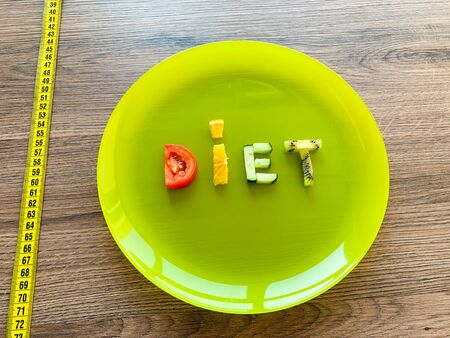 Word DIET made of sliced vegetables in plate with measuring on wood background. Stock Photo