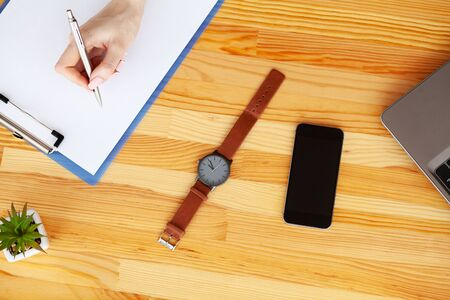 Contract. Blank of paper is on a wooden desk. Blank a4 paper is in the middle of wood office desk table with supplies. Top view with copy space, flat lay. Stock Photo