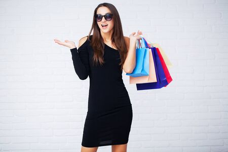 Shopping. Women holding colored bags on ligth background in black friday holiday