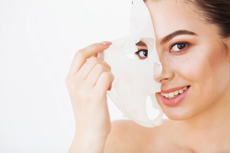 Spa and rejuvenation concept. Close up shot of attractive smiling woman removes paper mask from face, satisfied with its effect