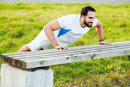Portrait sporty man 30s in sportswear doing push-ups in green park