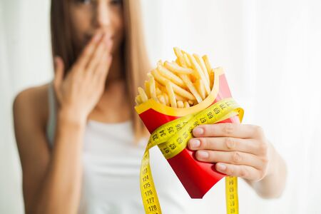 Diet. Woman standing on scales and holding a potato chips. The concept of healthy eating. Healthy Lifestyle. Diet 免版税图像