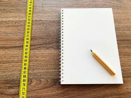 Diet concept. Measuring tape on wooden background with book diary notepad and pen for healthy fitness background