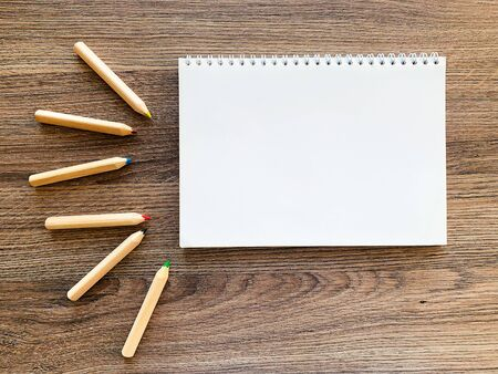 Top view office desk with Empty notebook and pencils on wood table Banco de Imagens