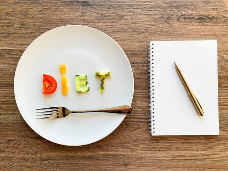 Word DIET made of sliced vegetables in white plate and diet plan on wood background