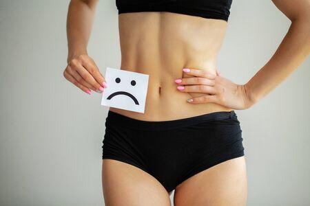 Woman Health. Female Body Holding Sad Smiley Card Near Stomach Stock Photo