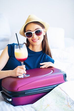 Beautiful woman with cocktail and suitcase on bed in hootel room