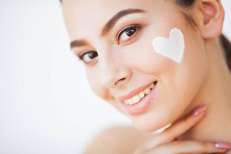 Protección de la piel. Bella modelo aplicando tratamiento de crema cosmética en su rostro