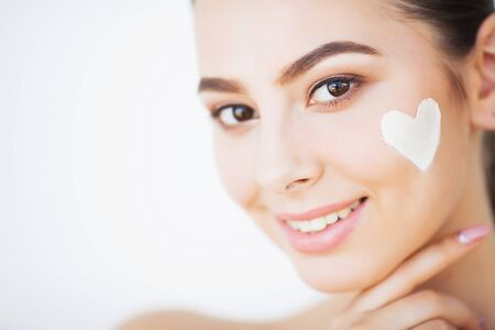 Skin Care. Beautiful model applying cosmetic cream treatment on her face 版權商用圖片