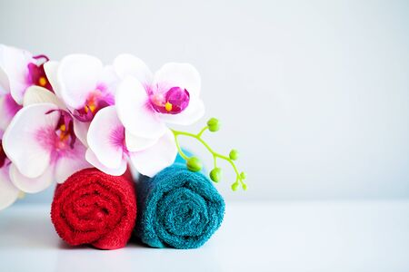 Colored towels and orchid on white table with copy space on bath room background. Imagens