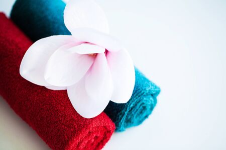 Colored towels and orchid on white table with copy space on bath room background.