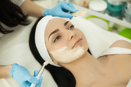 Woman receiving professional brush peeling in the cosmetology office