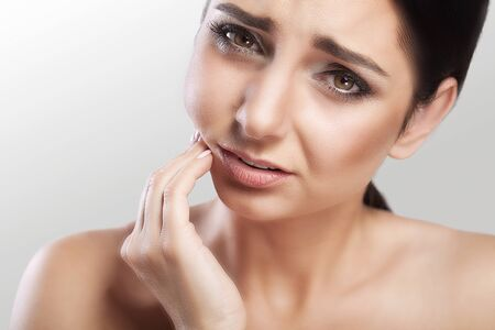 Beautiful young woman suffering from a toothache on a gray background, caries, dental problems, painful sensations on her face, beautiful makeup. Stock Photo