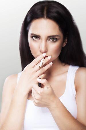 Eine Zigarette rauchen. Junges schönes Mädchen, das eine Zigarette raucht. Das Konzept der Gesundheitsversorgung. Raucherbar. Auf grauem Hintergrund.