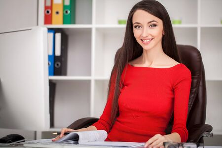 Smiling business woman in red dress sitting and writing something by the table as well as looking at camera