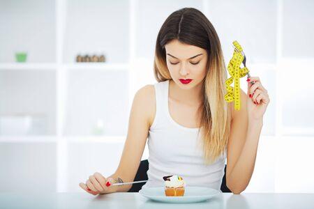 Diät. Hungriges Mädchen der Frau mit gelbem Maßband hält in der Hand Kuchenkleinen Kuchen. Gewichtsverlustdiät oder süßes Essen und Glückskonzept.