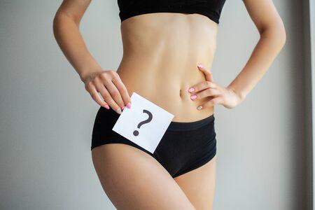 Health. Woman Body In Underwear With Question Card Near Belly.