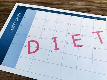 Diet plan concept. Measuring tape and diet plan on wooden background. Foto de archivo