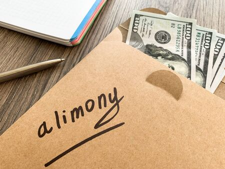 Divorce and separation concept. Alimony written on an envelope with dollars. 免版税图像