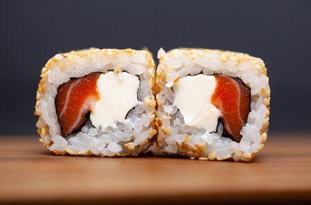 Rouleau de sushi japonais au saumon et concombre sur fond sombre