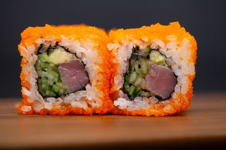 California rolls with salmon and cucumber on dark background.