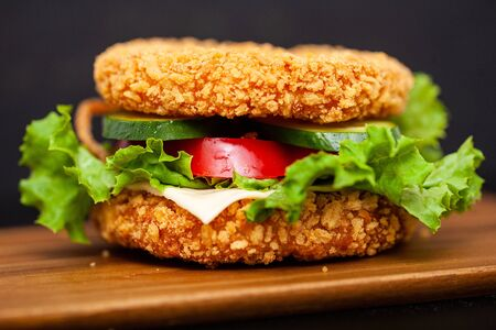 Sushi Burger with a variety of tasty ingredients on a dark background