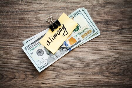 Payments alimony. Pile Dollars with sign alimony and money. Divorce and separation concept