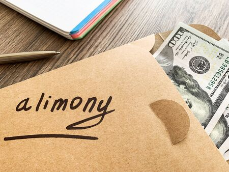Payments alimony. White envelope with sign alimony and money.