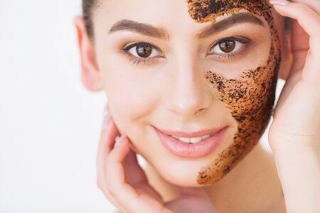 Cuidado de la piel facial. Joven encantadora hace una máscara de carbón negro en su rostro Foto de archivo