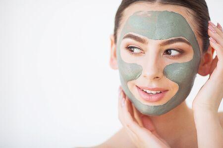 Protección de la piel. Mujer joven con máscara de arcilla cosmética sosteniendo pepino en su baño