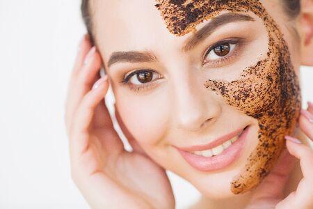 Cuidado de la piel facial. Joven encantadora hace una máscara de carbón negro en su rostro