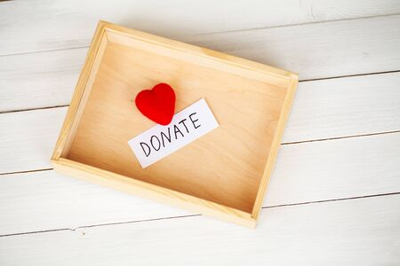 Donations and Charity. Donation Concept. Box of Donations and Heart on the White Background.