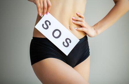 Vaginale of urineweginfectie en problemen concept. Jonge vrouw houdt papier met SOS boven haar kruis.