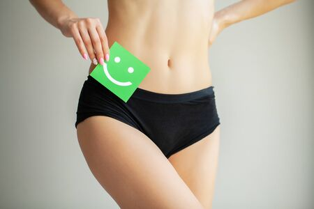 Woman holding paper with smile mark over her stomach. Health hygiene sexual education concept. Stock Photo - 128002162