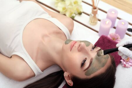 Spa therapy for young woman having facial mask at beauty salon - indoors Stockfoto