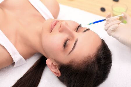 Woman gets injection in her face. Beauty woman giving injections. Young woman gets beauty facial injections in the cosmetology salon. Face aging injection. Aesthetic Medicine, Cosmetology