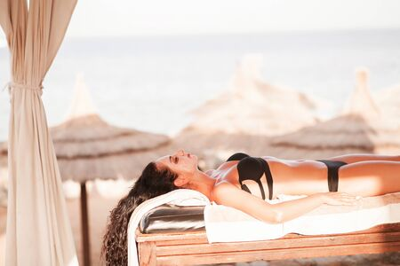 Spa and massage. Pretty woman in spa salon in sunny beach get face and back massage. High quality.