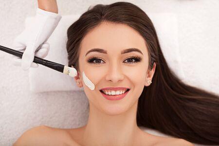 Hermosa mujer joven recibiendo un tratamiento facial en el salón de belleza.