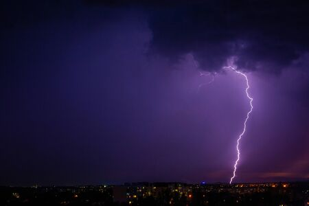 Lightning strikes storm over city purple light.