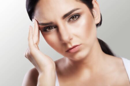 Pain. Depressed overweight is a beautiful young woman with black hair who suffers from severe headaches and a touching head. Migraine. Treatment. The concept of health.