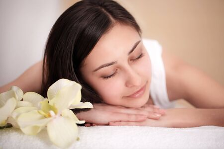 people, beauty, spa, healthy lifestyle and relaxation concept - close up of beautiful young woman lying with closed eyes and having face or head massage in spa Фото со стока