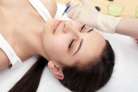 Vrouw krijgt injectie in haar gezicht. Schoonheidsvrouw die injecties geeft. Jonge vrouw krijgt gezichtsinjecties voor schoonheid in de schoonheidssalon. Gezichtsveroudering injectie. Esthetische geneeskunde, cosmetologie Stockfoto