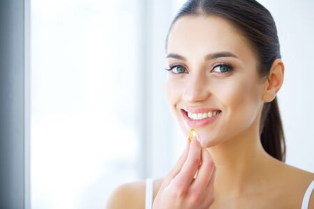 Beautiful Woman Holding Fish Oil Pill In Hand. Healthy Nutrition Stock fotó - 129838468