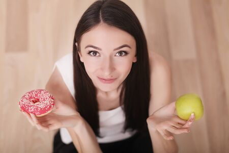 Diet. Woman Measuring Body Weight On Weighing Scale Holding Donut and apple. Sweets Are Unhealthy Junk Food. Dieting, Healthy Eating, Lifestyle. Weight Loss. Obesity. Top View Stock Photo
