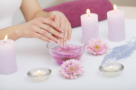 Spa Beauty Salon. Closeup Of Female Hands With Perfect Natural Fingernails Soaking In Hand Bath Before Manicure. Woman Washing Perfect Nails In Transparent Bowl Of Water. Nail Care. High Resolution 写真素材